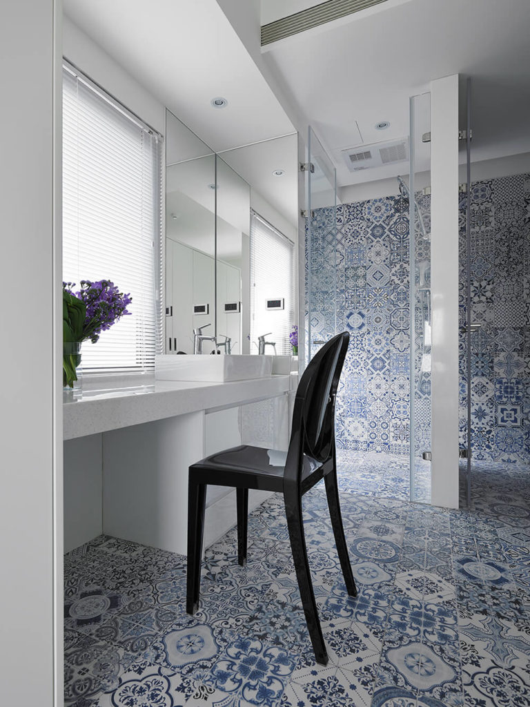 This bathroom is equipped with a walk-in shower and large vanity space. The white walls and minimalist design of the home are contrasted by the intricately patterned blue tile here.
