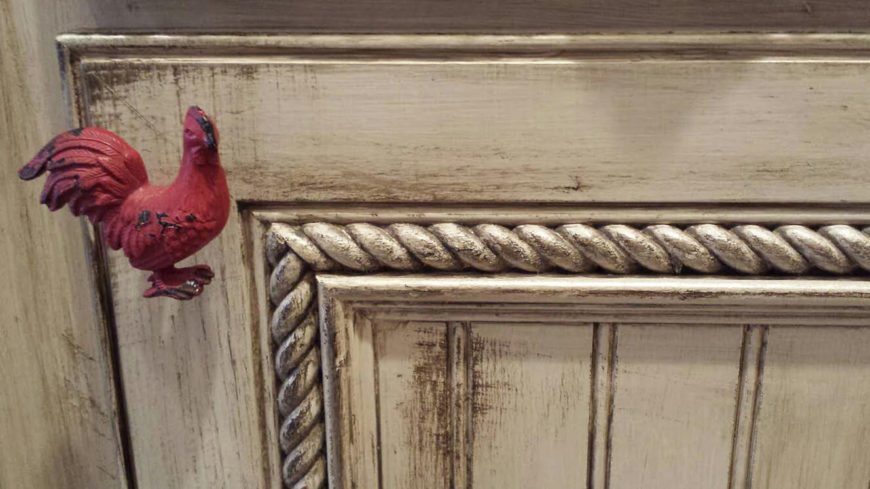 Here's a close look at that beautiful rope trim adorning the cabinetry. This gives the wood a timeworn, lived-in look, and works perfectly with the antiquing. The bright red rooster handle is a unique touch seen on the island.