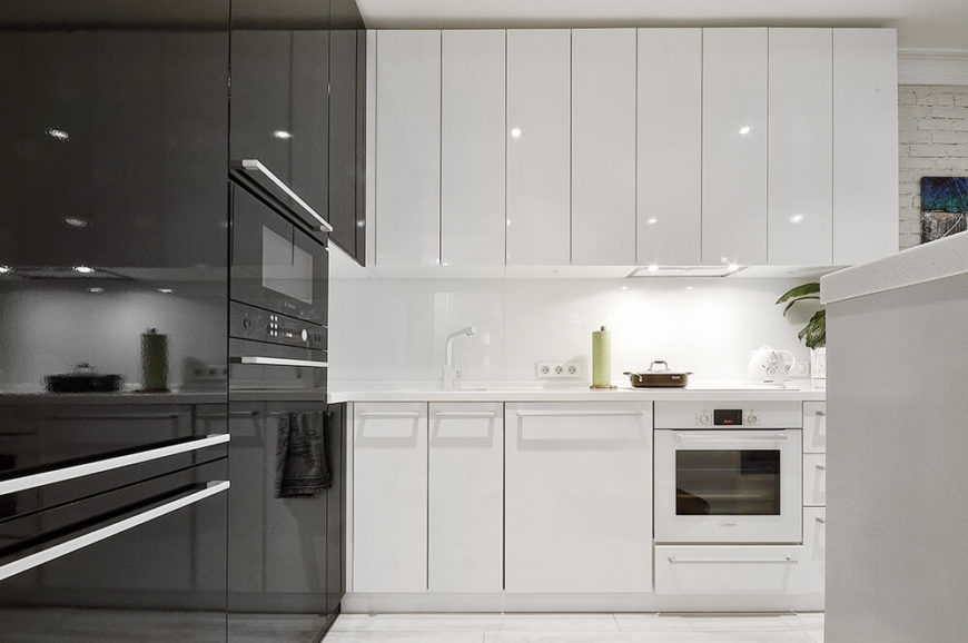 Upon entering the main living space, we turn right and are met by the incredibly modern and minimalist kitchen in white and black. The glossy cabinetry helps reflect light around the room and makes the apartment feel larger.