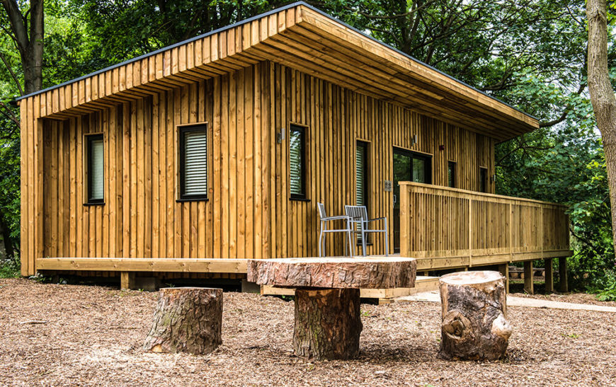 Here we see one of the outsides of the eco-lodges, which are wood and glass construction. A narrow porch allows guests to enjoy the outdoor weather in the evenings. In front, a rustic table and stump seating adds to the natural atmosphere.