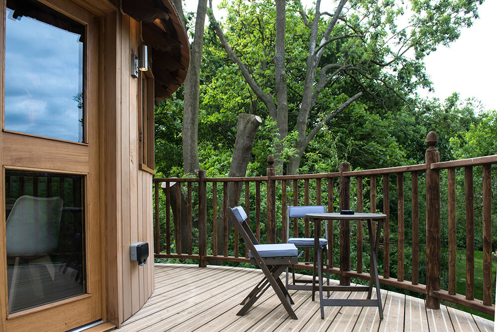 This deck features a small coffee table set overlooking the beautiful greenery outside.