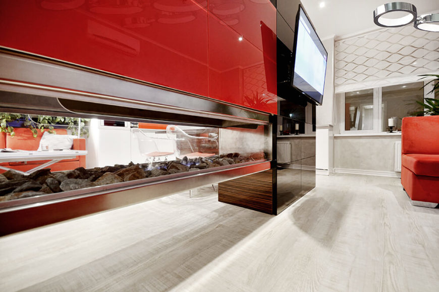 Seen from the side, we can witness the cool floating motion of the fireplace. The entire central element is wrapped in glossy red and black paneling. To the right, a mounted television faces the open living room.