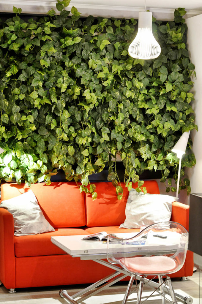 Here we see one of the bright orange sofas backed against the unique wall garden, with lush greenery spilling over the back. This feature adds a healthy dose of organic messiness to the ultra-clean look of the home.