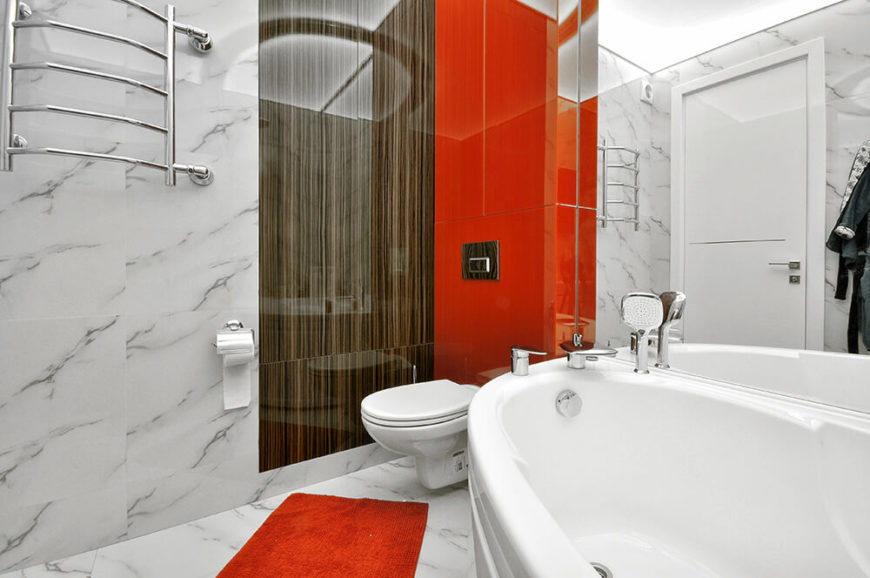 The bathroom combines many of the elements seen throughout the rest of the home, including sleek glass, bold orange tones, and a bit of natural wood.