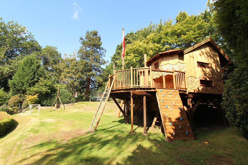 Set against the foliage at the rear of the landscape, the treehouse is a sight to behold and an unobtrusive presence at the same time. Here we see the rope and climbing walls, as well as a peek at the secret entrance below the deck.