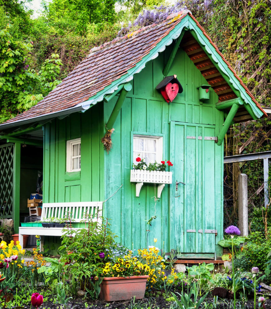 This bright spring green shed has adorable white details and a cedar roof. Tucked into the corner of this garden, it's surrounded by color or natural beauty.