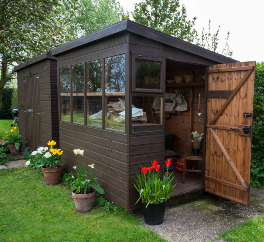 Square awning windows provide ample light for potting projects in this slant roofed gardening shed.