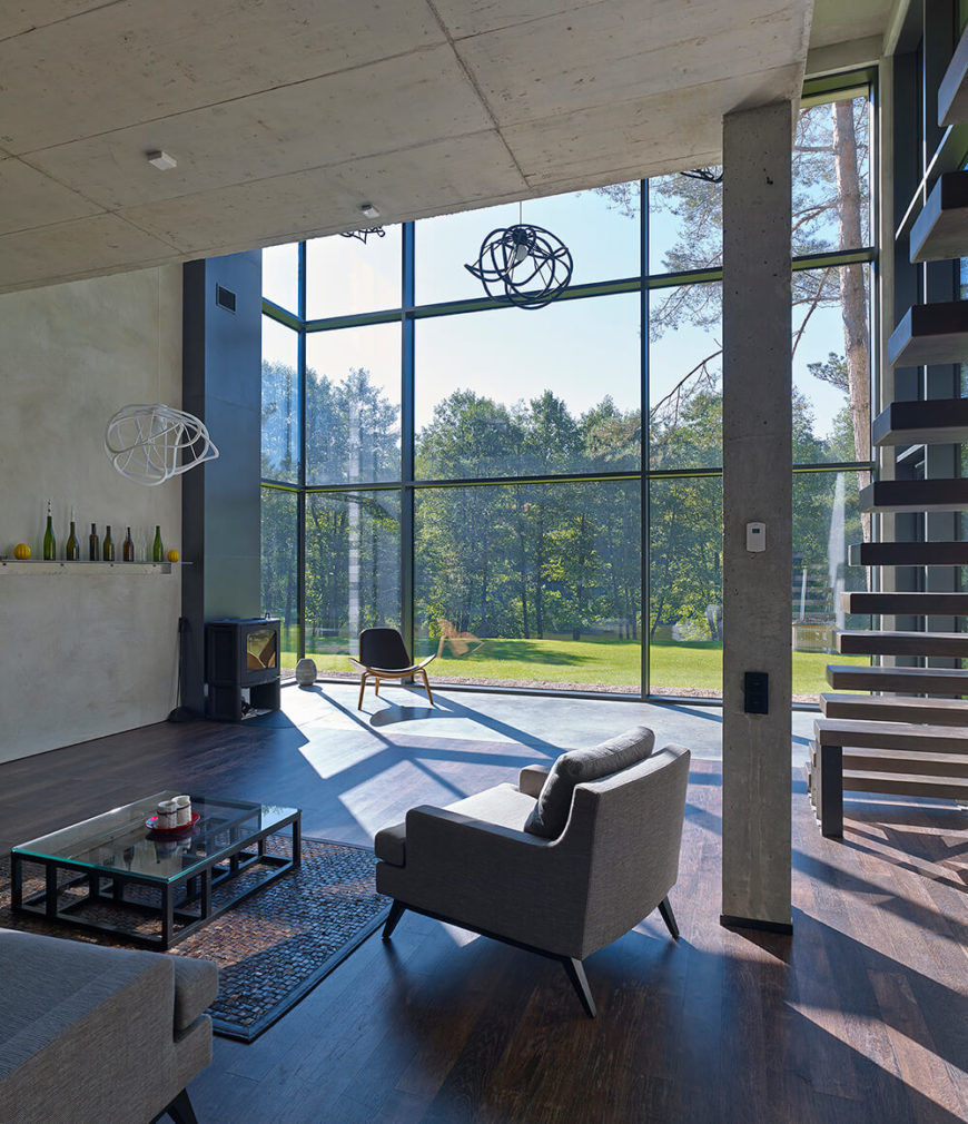 Here we have another look at the spacious living room, in which we can see several more distinct seating areas. One, by the fireplace, looks out through the massive glass panels into the forest. The other is a more traditional seating area with a glass coffee table.