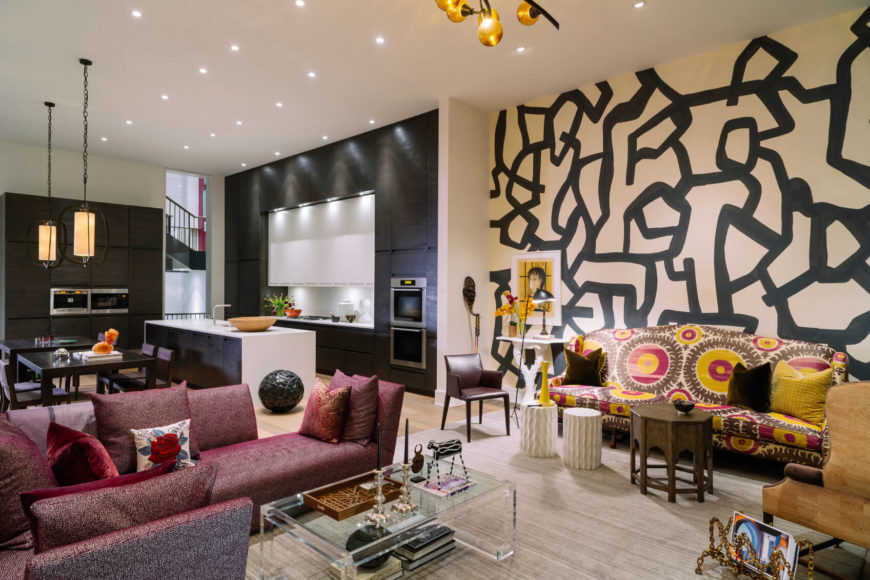 This room has a darker black and off white backdrop for warmer colored furnishings. The room is almost divided by the color theme. One side is covered in a deeper red, while the other has a good splash of yellow.