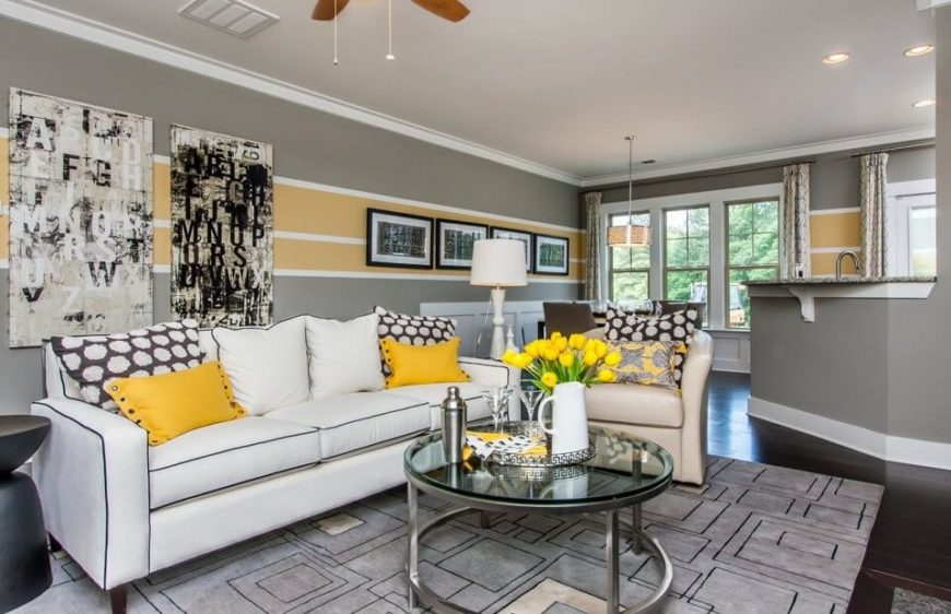 This living room has a number of whites and grays with the accent of yellow to to bring a deal of vibrance. Monochrome rooms are great and classic places for a single color to stand out.