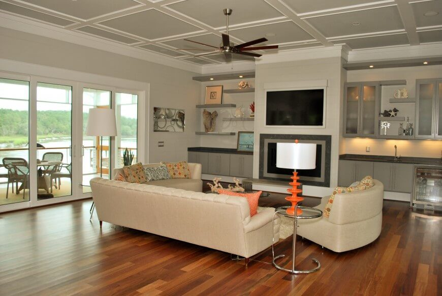 This room features an understated cream palette with orange accents. The orange bring a glowing warmth the creams and off whites, giving a warm lit and cozy illuminated look.