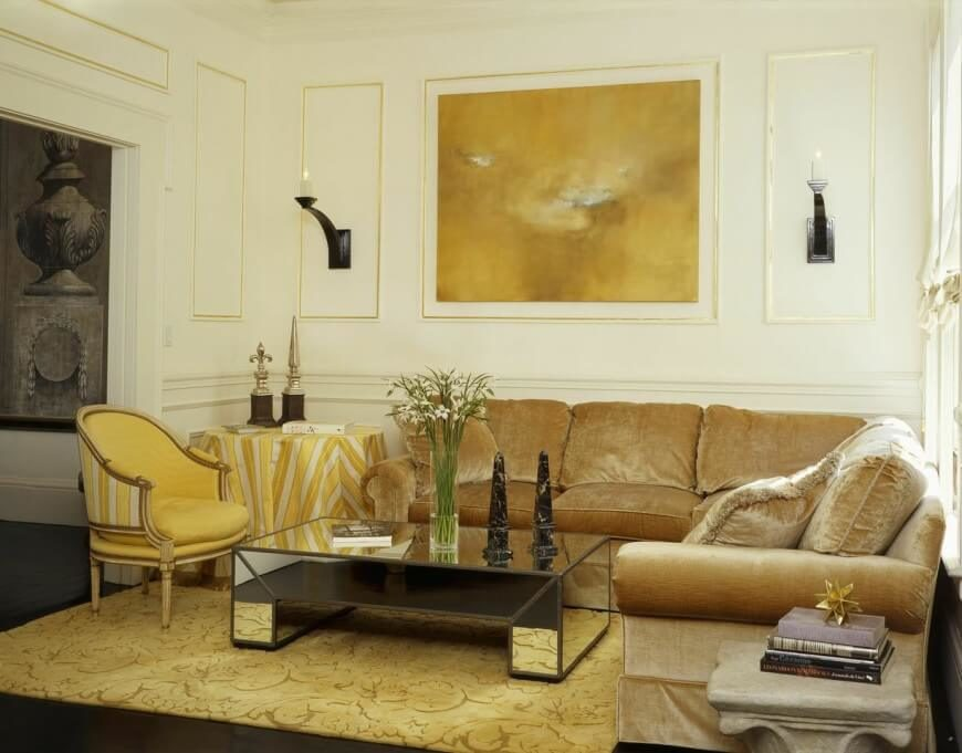 There is a good use of reflective surfaces and gold to build a very luxurious living room.