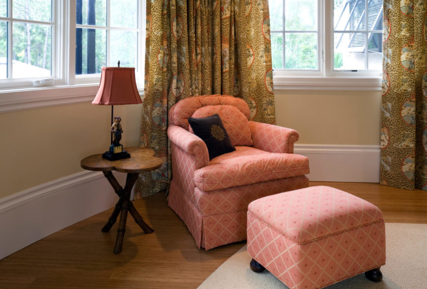 This nice and cozy seat has a matching square ottoman and is sitting in the corner of this room. The ottoman adds a lot to this chair, making it more inviting and adding a splash of color to the room.