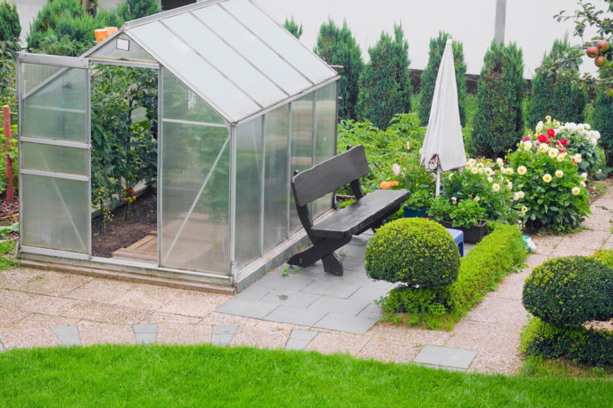 This simple and personal greenhouse is surrounded with nice landscaping and a bench to relax on while you enjoy the fruits of your labor.