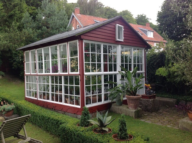 A greenhouse does not need to be entirely covered in the glazing material. Here is a greenhouse with a more involved frame. With a design like this, the greenhouse can easily match with the other buildings on your property.