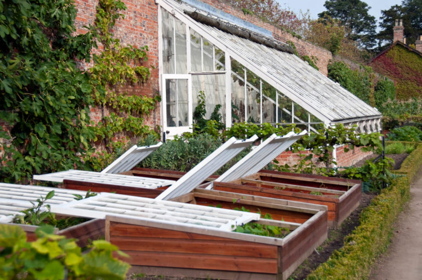 This is a good example of an attached greenhouse with a sturdy brick base. In addition to the greenhouse there are planter boxes that provide even more space for growing.