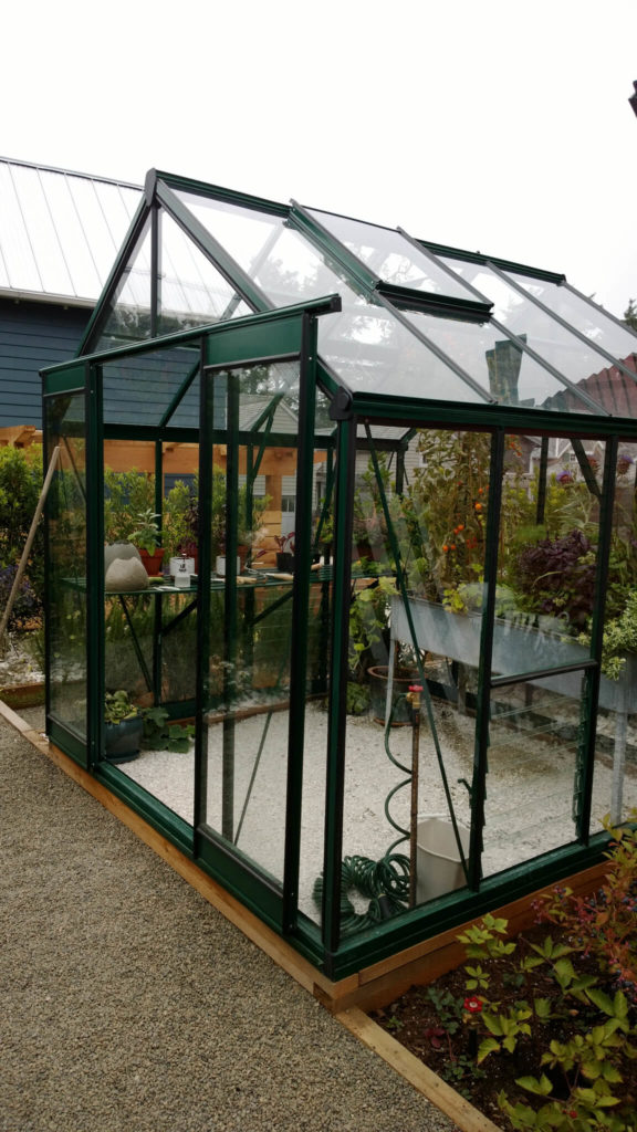 This is a small but high quality greenhouse in the middle of a garden area. It has sliding doors, extra vents, and a loose stone base. The colored frame makes this greenhouse sleek and stylish.