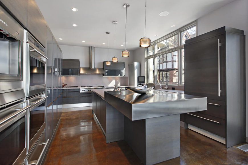 An entirely metal kitchen with stainless steel appliances and a two-tier brushed nickel island.
