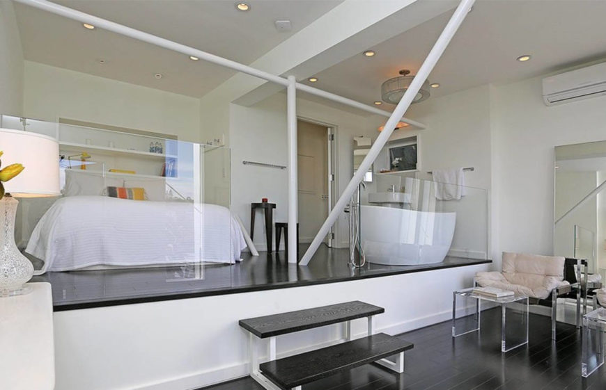 This much more modern example is bedroom, bathroom, and sitting area all encased in glass balustrades. The whole of the room is in light colors, with contrasting dark floors. The glass balustrades keep the sections separate, but prevent them from feeling enclosed
