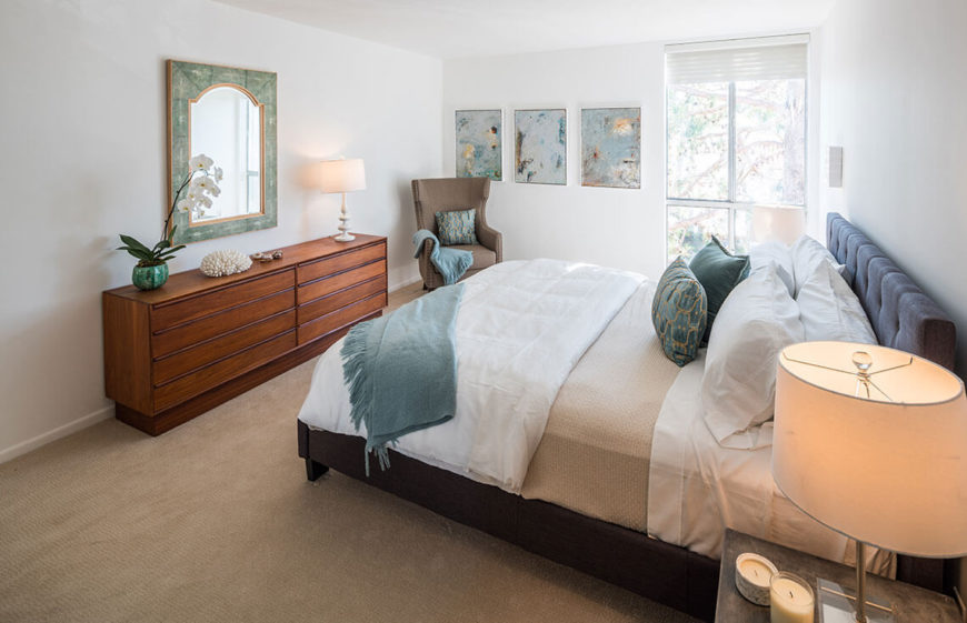The bedroom is seen from a different angle, highlighting the decorative mirror and small displays on the dresser. Exotic and beachy elements are combined to give the bedroom a sense of a vacation getaway.