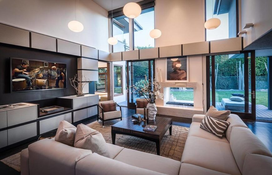 In this angle of the same space, we can see the unobstructed windows and doors, that are letting in the sunlight. Also we see that the furniture is focused toward a built in entertainment center and shelves. Buyers love these areas, and focusing furniture toward them is always smart