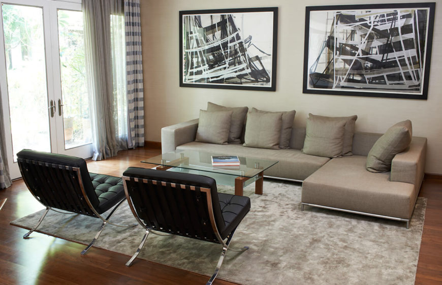 Twin chairs and pieces of art work to build a welcoming symmetry in this well lit and simply designed living room.