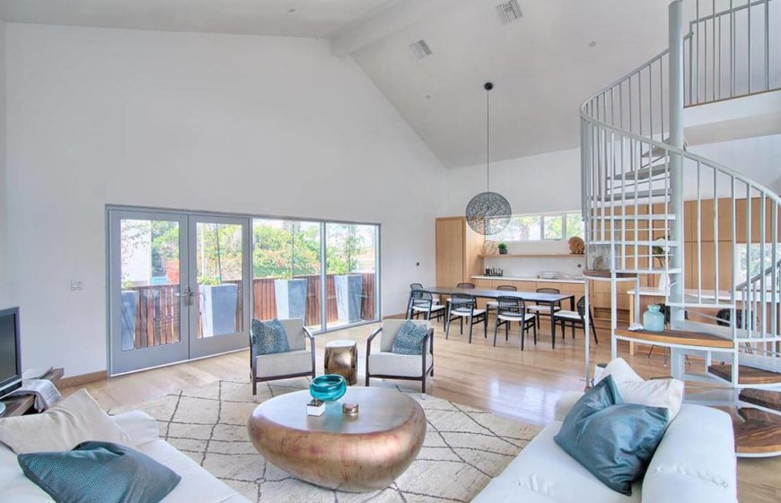 This is a fabulous open living room with plenty of natural light and bright colors. The limited but tasteful staging items on the table as well as the built in shelves under the stairs accentuate the features without being too distracting.