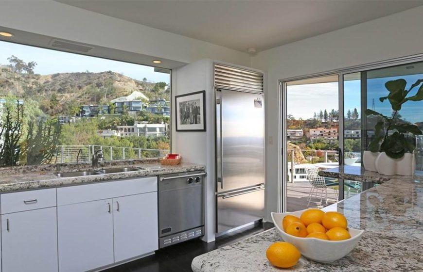 This clean and well lit kitchen is perfectly staged, We can see that there are not a number of appliances cluttering up the countertops. The counters only have a simple attractive accessories. Things that remind you it's a kitchen, such as a bowl of fruit, but not that show the full functionality of the kitchen. Remember a staged kitchen is not a functional kitchen, but an attractive kitchen.