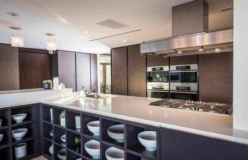 Modern kitchen with white countertops and open cube storage behind the bar.