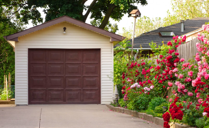 Use roses to line the driveway to give the ultimate welcome home view. These red and pink roses help to soften the otherwise plain garage.