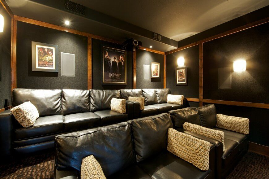 Cozy sofas and loveseats are seating in this home theatre, which is decorated with only a few movie posters. Dark walls help enhance the movie theatre feel.