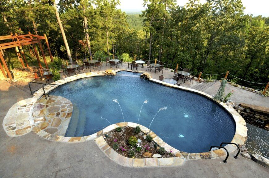 Here is a concrete pool in the traditional kidney shape, with a water feature. This is an amazing example of how a concrete pool can be customized.