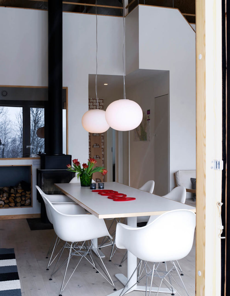 The white dining table and modern curved chairs exemplify the modern minimalist outlook of the home, surrounded by white walls and accents of light natural wood. The flooring is bleached to a light tone, meshing well with the walls.