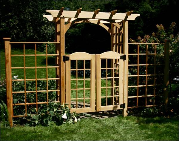 A simple wooden pergola-topped gated arbor with fence sections on either side. This arbor is great for any backyard, particularly for homes that have an Asian flair.