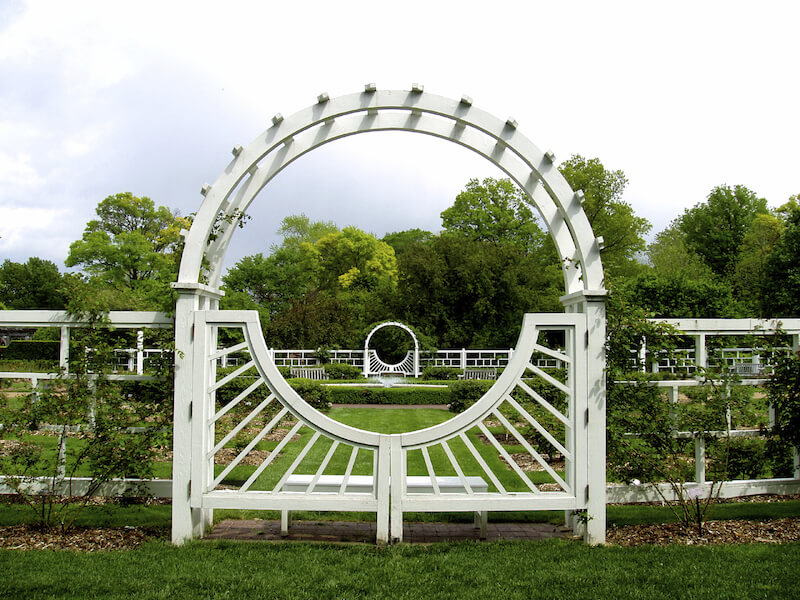 A thick white wooden arbor with a single gate attached to a modern style decorative fence. The sunburst design on the gate is gorgeous.