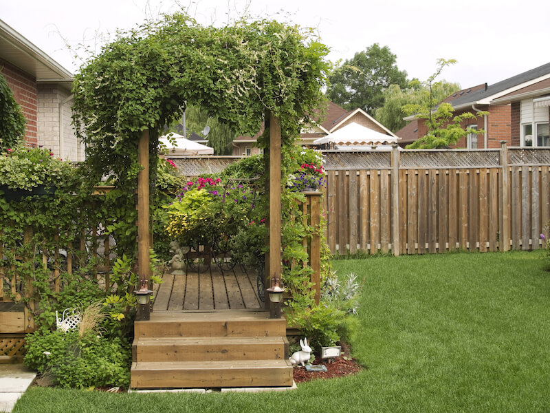 An arbor marks the entrance to the deck from the backyard, and the whole of the deck is swathed in lovely, fragrant flowering vines.