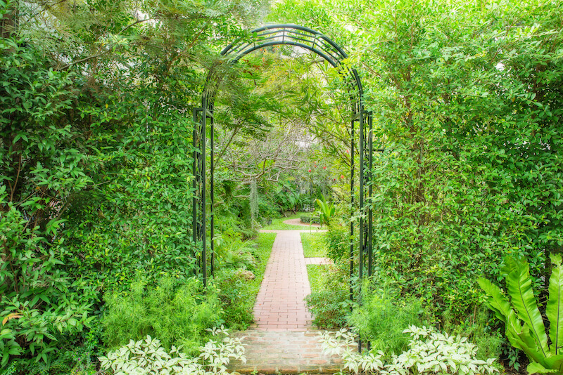 A simple metal arbor blends neatly into the thick foliage along this brick walkway.