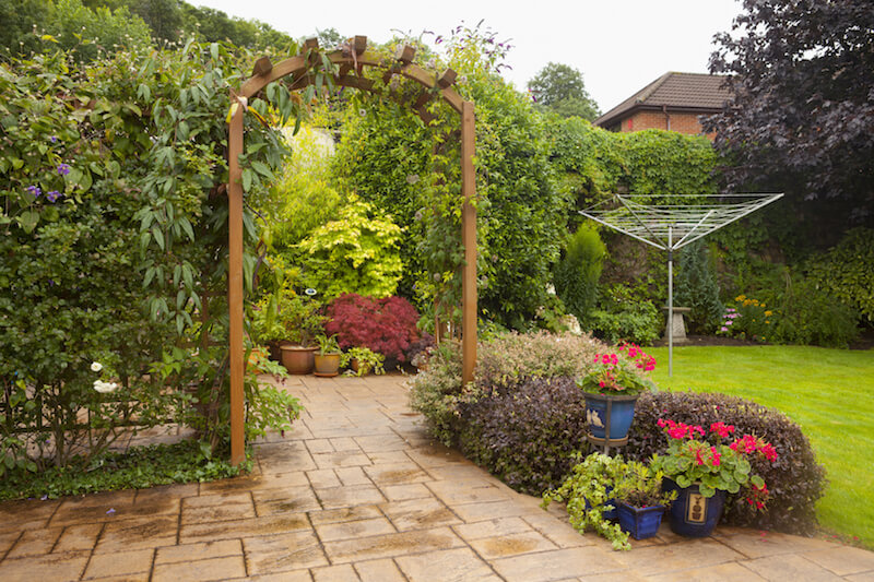 A simple cedar arbor with an attached screen on either side that are fully covered in vines. The shrubs are paired with simple containers filled with flowers.