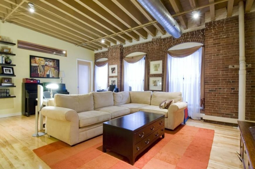 Here is an room with an exposed beam ceiling. An exposed beam look works very well with exposed brick and duct work to make an unfinished, laid back, care free, and relaxed appeal to a room.