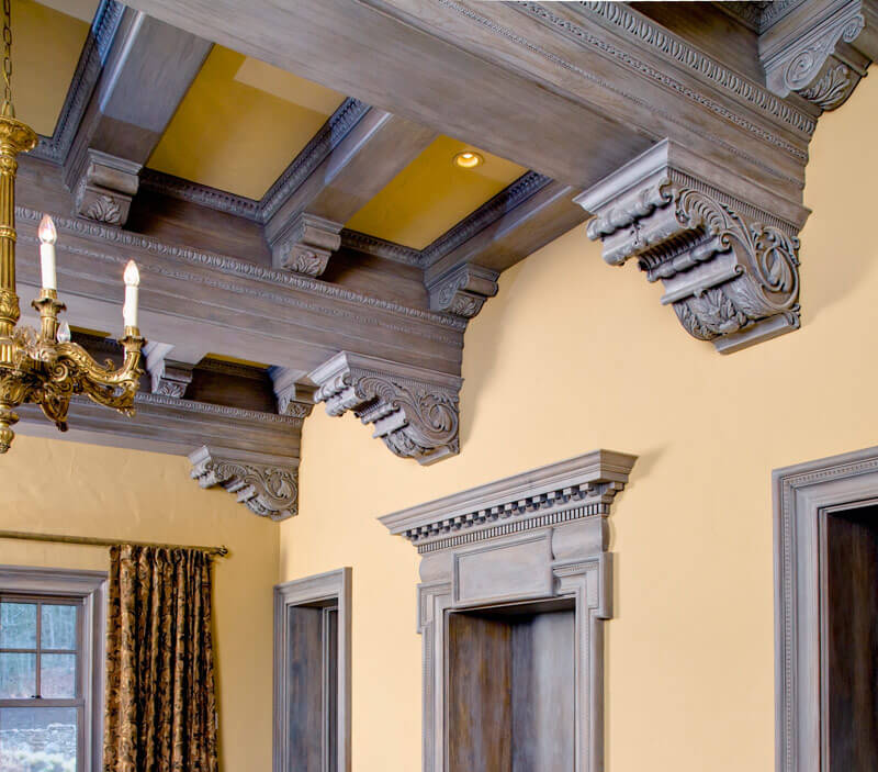 This very detailed and elegant ceiling has a coffered ceiling with finely crafted adornments. These give this room a very elevated and high end look. These kinds of elements are best if they are hand crafted, so that you know that they are quality and last for some time.