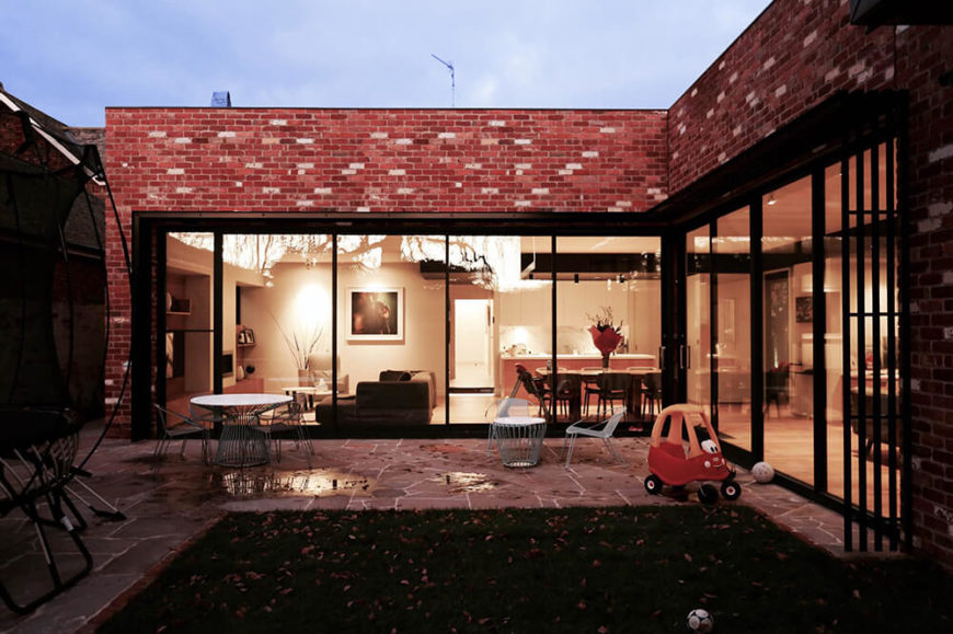 Moving back outside, we see the grand L-shape of the structure, wrapping the cozy courtyard. Full height glass panels all around make for an intriguing fluidity of space between indoors and out.