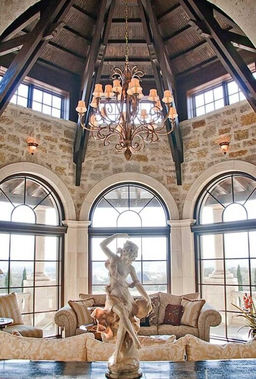 Another luxury living room with a stunning chandelier and marvelous exposed brick walls. The massive windows ensure a great deal of natural light during the day. The chandelier is helped by a bit of sconce lighting that sit on top of the windows.
