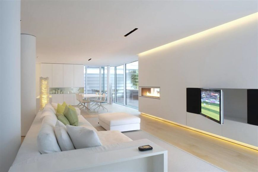 This living room uses a bit recessed lighting, but the majority of the light is coming in through the large windows. The recessed lighting is giving just a bit of help to the natural light in the day, but at night, these lights will light up this room without being in the way. Also, rope lighting is used near the bottom of the wall to add a bit of a design feature.