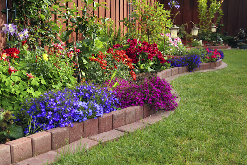 Here is a brick lined flowerbed against a fence in this yard. Placing a flower bed against a fence is an amazing way to keep your yard space open, as well as adding some appeal to your fencing.