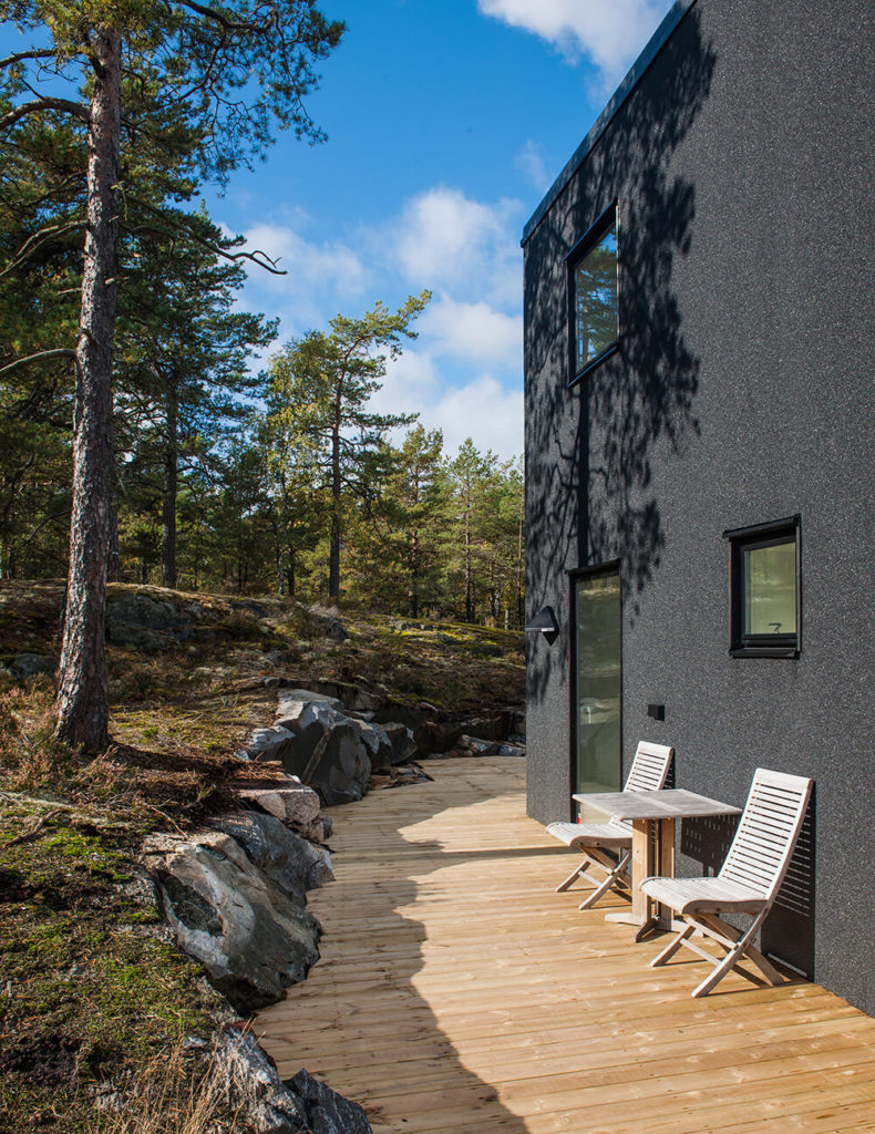 In this exterior shot, we can see the light natural wood deck surrounding the home, helping set it directly into the rocky terrain. The high contrast black exterior stands out against the nuanced landscape.