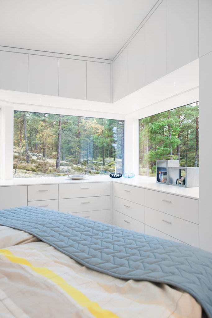 The bedroom features a suite of built-in cabinetry and drawers, making for subtly blended-in storage options. Large corner windows offer more expansive natural views from indoors.