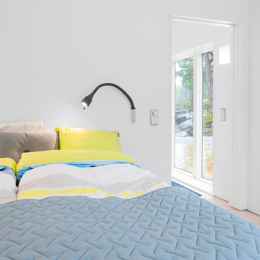 The primary bedroom features subtle use of color, with light blue and yellow bed sheets paired with the same white walls seen elsewhere in the home. Through the doors at right, we can see large glass sliding doors that lead to the patio.