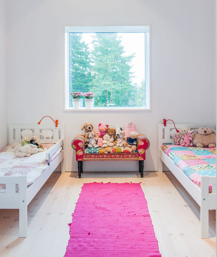 Small girl's bedroom with a small twin bed set on the hardwood flooring topped by a pink rug.