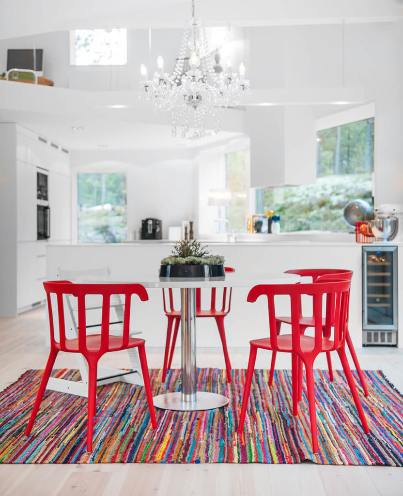 Across the rainbow rug and bright red dining room set, we see the sleekly designed, open plan kitchen below a loft area. This space is illuminated by natural light via sets of large windows all around.