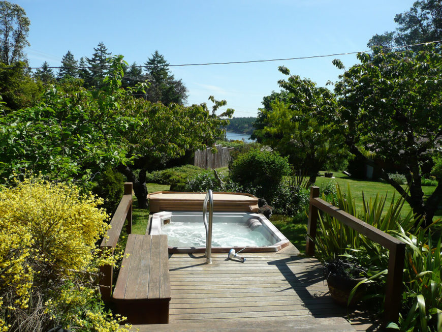 Here is a deck that has a hot tub off of the end of it and a small bench on the side. There is plenty of greenery and vegetation around. This is a serene and relaxing spot to let the world disappear.